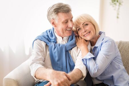 Happy mature couple enjoying time at home and relaxing on sofa