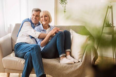 Romantic senior couple sitting close together on sofa, enjoying weekends at home Stok Fotoğraf