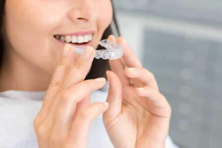 Dental Treatment Concept. Cropped image of young woman holding invisible braces, whitening tray, free space