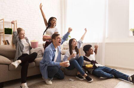 Junge Fußballfans. Freunde jubeln für ihre Lieblingsmannschaft und schauen sich das Spiel zu Hause mit Popcorn an Standard-Bild
