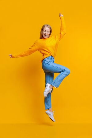 Hooray. Happy young girl jumping in studio and looking at camera on orange background with copy space