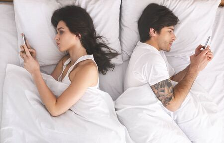 Problems of millennial couple. Young spouses using cellphones, ignoring each other in bed, top view Banque d'images - 131916982