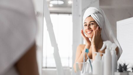 Skincare And Beauty. Happy Girl Applying Eye Cream On Skin For Wrinkles Prevention Standing In Bathroom. Selective Focus, Panorama