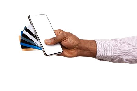 Online banking. Smartphone with blank screen and few credit cards in black male hand over white background Banco de Imagens