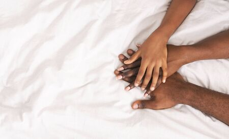 Family unity. African father, mother and daughter stacking hands together over white bed sheet background, panorama with copy space
