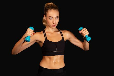 Determined Fit Woman Exercising With Dumbbells Over Black Background. Strength Workout Concept. Studio Shot