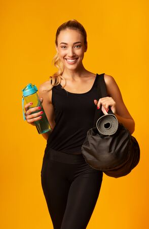 Smiling Girl Holding Fitness Bag And Bottle Of Water Looking At Camera Standing Over Yellow Background. Studio Shot