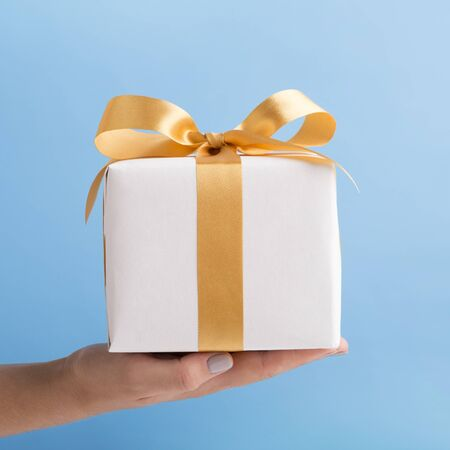 Holiday presents. Woman holding white present box with gold ribbon over blue background Stock fotó