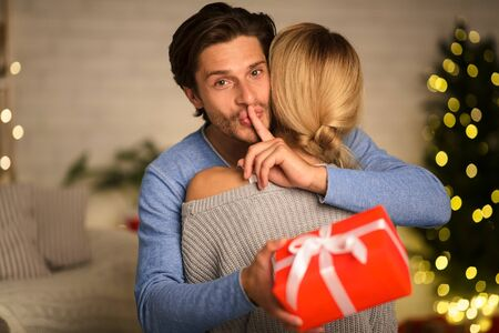 Shh Husband giving Christmas present to wife, embracing her and making silence sign