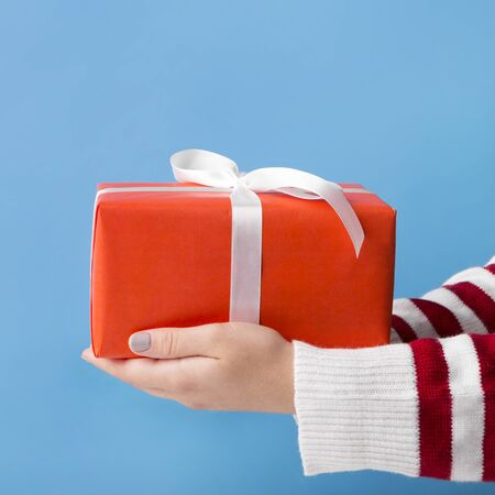 Giving presents. Woman holding Christmas present on blue background Foto de archivo - 132081268