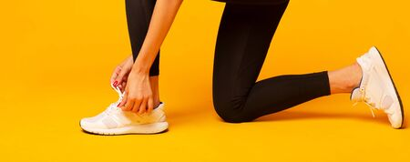 Fitness Fashion. Unrecognizable Girl Lacing Shoes For Workout Over Yellow Background In Studio. Cropped, Panorama Stock fotó