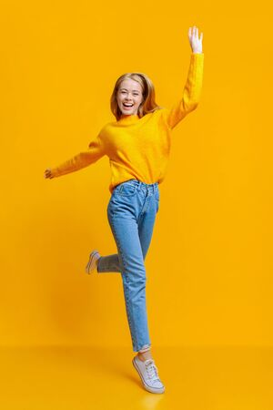 Wait for me. Positive teenage girl walking on air over orange studio background
