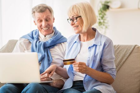 Commercio elettronico. Coppia matura utilizzando laptop e carta di credito, acquistando cose su Internet Archivio Fotografico