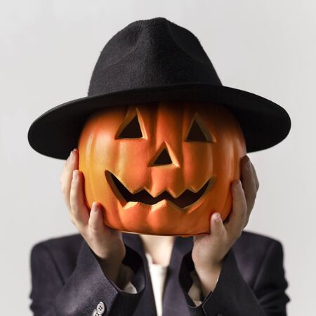 Halloween costume party. Man holding Jack o Lantern head in black hat over his face, gray background