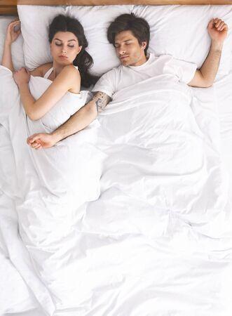 Niezadowolona kobieta nie może spać z mężem, który wyciąga szeroko ręce w łóżku, widok z góry, pusta przestrzeń