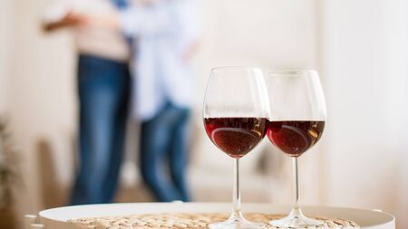 Loving couple dancing with glasses of red wine on foreground, celebrating their anniversary at home Standard-Bild - 131720187
