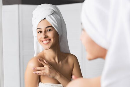Body Care. Young Woman With Towel On Head Touching Shoulder Applying Lotion Standing In Bathroom. Selective Focus