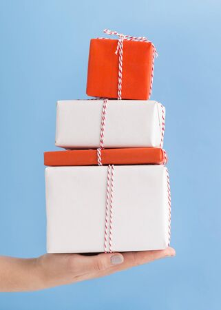 New Year presents in boxes for Christmas in woman hand on blue background Foto de archivo - 132081562