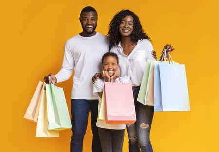 Viernes negro. Retrato de familia afroamericana sonriente con bolsas de papel feliz después de compras exitosas, fondo amarillo studio