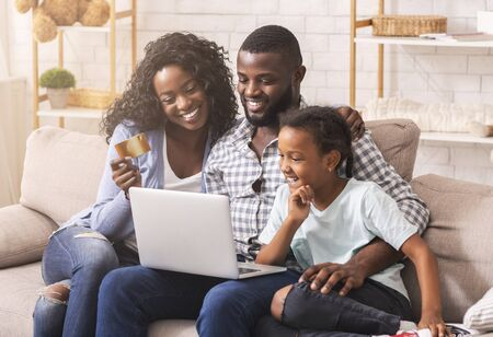 Online Shopping. Happy Black Mother, Father And Daughter Using Laptop And Credit Card, Buying Goods In Internet, Sitting On Sofa At Home.