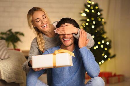 Sorpresa navideña. Mujer amorosa dando regalo al marido, cerrando los ojos desde atrás
