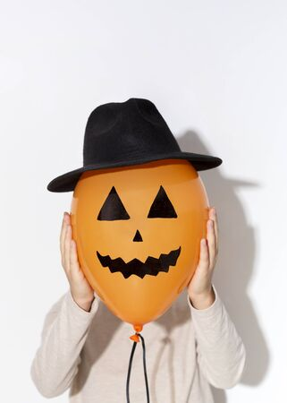 Halloween photo. Woman change her face on orange balloon in hat on white background, copy space