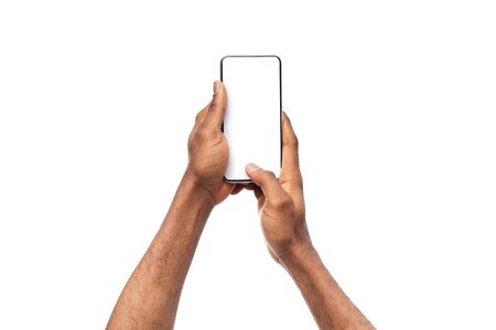 Black mans hands holding mobile phone with blank screen, taking photo on white background, copy space