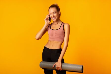 Happy Lady Talking On Phone Holding Fitness Mat Smiling At Camera Standing On Yellow Background. Studio Shot Stok Fotoğraf