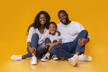 Beautiful african american family sitting on floor and smiling over yellow studio background, copy space Banque d'images