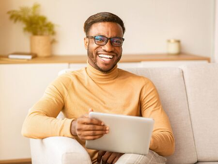 Happy African American Guy Using Digital Tablet Smiling At Camera Sitting On Sofa Indoor. Selective Focus
