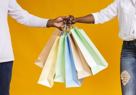 Family shopping and sales concept. Lots of shopping bags in hands of african american couple, closeup