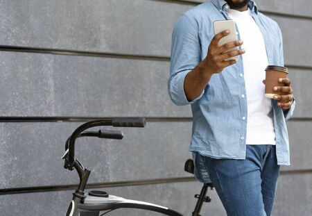Unrecognizable black man with bicycle browsing internet on smartphone and drinking takeaway coffee outdoors Stock fotó