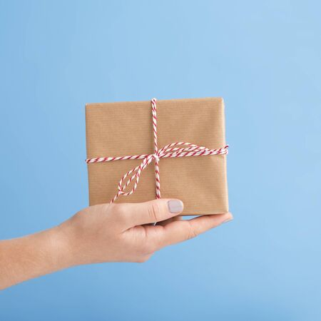 Eco friendly. Close up of Holiday gift in box on woman hand, blue background Foto de archivo - 132081702