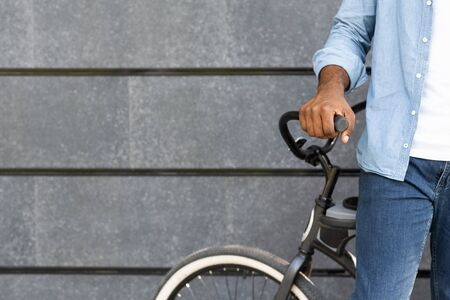 Unrecognizable african american man standing near his bicycle against grey wall background, copy space Stock fotó