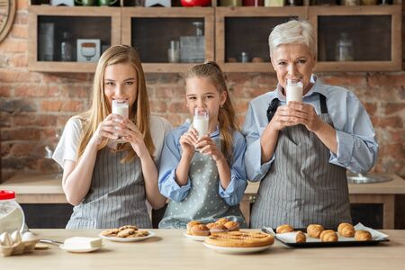 Daily doze of calcium. Healthy girl, mom and granny drinking milk in kitchen while cooking
