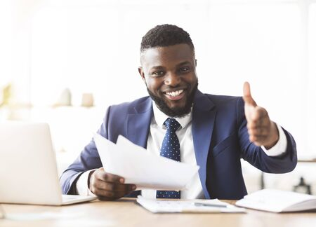 Partnership concept. Cheerful african american businessman holding documents and extending hand to shake, office interior, copy space