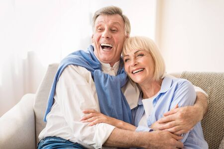 Senior couple laughing together, relaxing and embracing at home Stock Photo - 137214118
