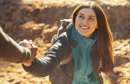 Portrait of pretty cheerful girl supported by man while hiking, close up