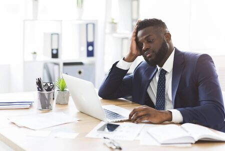 Exhausted young african american businessman working with laptop in office, touching his forehead, copy space