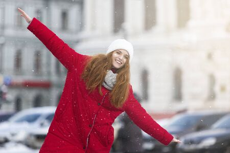 Positive young ginger girl having fun on winter street, imitating airplane with both hands, freedom and joy concept, free space