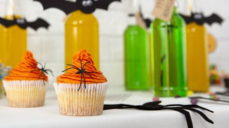 Halloween creative composition of healthy cupcakes and colored drinks in bottles on table, panorama