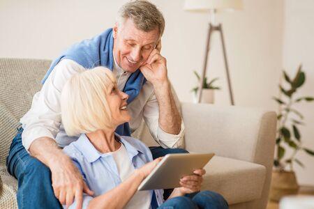 Happy elderly couple searching film on digital tablet, resting at home on weekends Standard-Bild