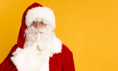 Ssh. Santa Claus on orange background holding finger near his mouth, copy space
