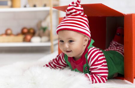 Christmas surprise. Adorable baby elf crawling out of gift box, looking at empty space