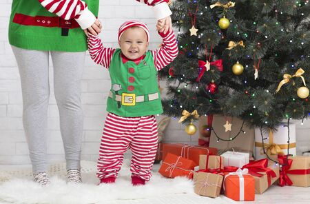 Santa helpers. Adorable baby elf standing with friend at Christmas tree with gifts, free space Stock Photo