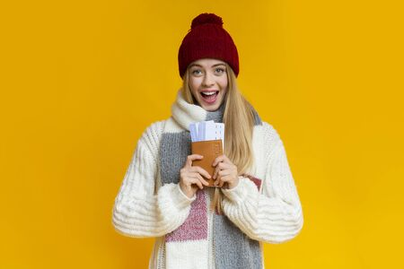 Excited girl wearing winter knitted set holding ticket and passport, yellow studio background, holiday travelling vacation concept 写真素材
