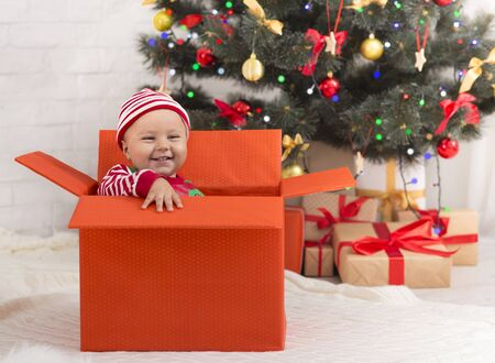 Xmas miracle. Cute baby sitting in big gift box under Christmas tree, empty space Stock Photo