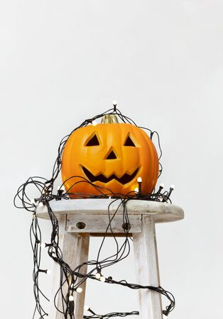 Halloween party. Orange pumpkin with lights garland on chair in flat, white background, copy space Zdjęcie Seryjne