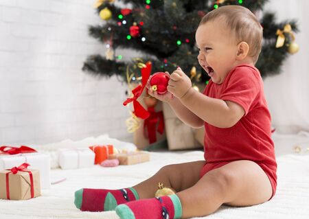 Unwanted gift. Furious emotional baby yelling, sitting with decorations near Christmas tree, empty space Stok Fotoğraf