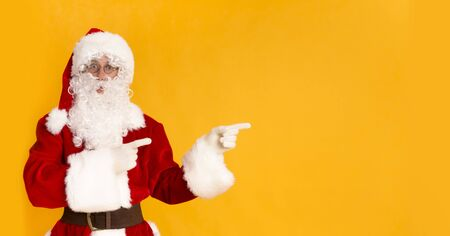 Christmas sales. Amazed Santa Claus showing on copy space on yellow background, panorama